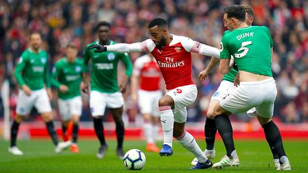 Arsenal's Alexandre Lacazette (left) and Brighton & Hove Albion's Lewis Dunk battle for the ball dur