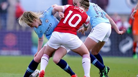 Manchester City's Caroline Weir, (left) battles for possession of the ball with Arsenal's Kim Little