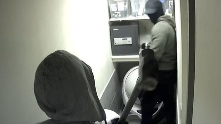 The armed burglars prepare to steal the safe.
