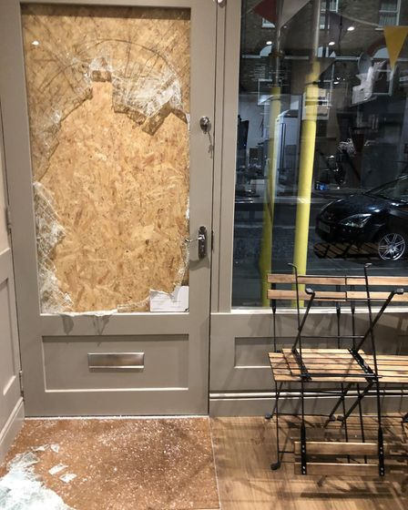 The front door of the cafe, which was smashed in during the raid.