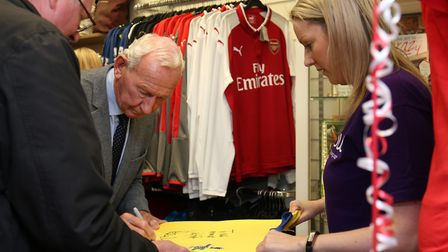 Former Arsenal goalkeeper Bob Wilson signs a shirt for a fan at the Arsenal Foundation takeover of t