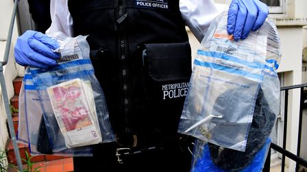 Police hold eveidence bags obtained from a Section 23 drugs warrant in N7 on May 17, 2019. Bags cont