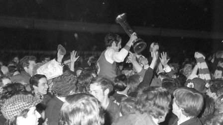 Arsenal captain Frank McLintock holds the Inter-Cities Fairs Cup aloft as he is carried from the pit