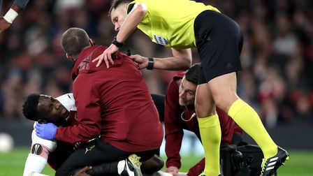 Arsenal's Danny Welbeck receives treatment after picking up an injury during the UEFA Europa League,