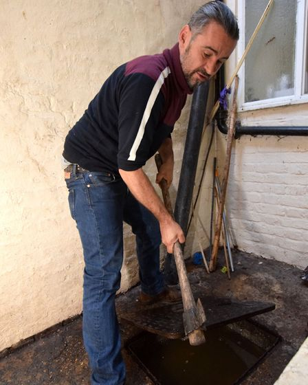 Petrit Gorovelli lifts the drain cover to see that the drains are still blocked and so the problem o