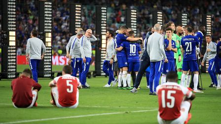 Arsenal players look dejected as Chelsea players celebrate during the UEFA Europa League final at Th