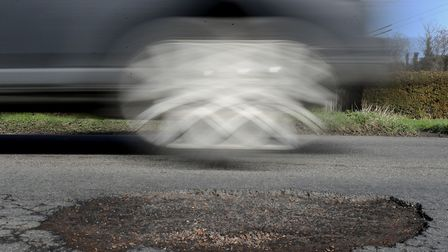 A file image of a car passing a pothole. Picture: Gareth Fuller/PA