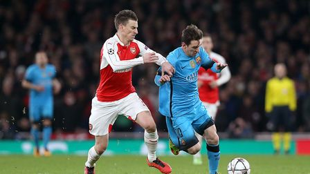 Arsenal's Laurent Koscielny (left) and Barcelona's Lionel Messi battle for the ball during the UEFA
