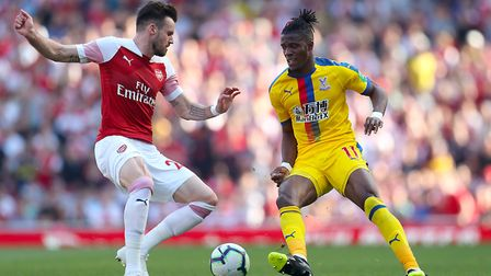 Arsenal's Carl Jenkinson (left) and Crystal Palace's Wilfried Zaha battle for the ball during the Pr