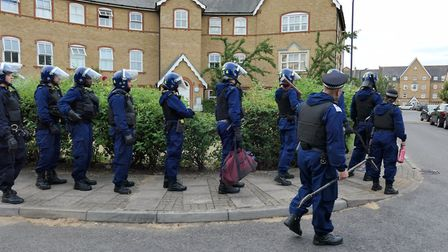 Riot police snake around a Wembley estate ahead of a dawn raid. Picture: David Nathan