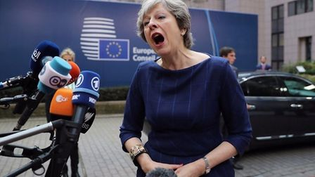 Theresa May appears to sing into a microphone. Photograph: PA.