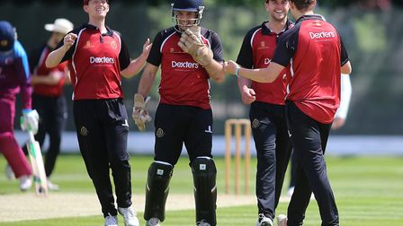 Luke Hollman is congratulated after he claims a wicket for North Middlesex in the Middlesex County P