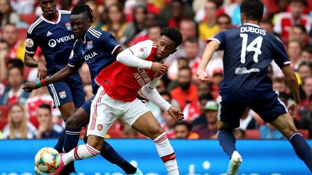 Arsenal's Reiss Nelson (second right) and Lyon's Bertrand Traore (second left) battle for the ball d