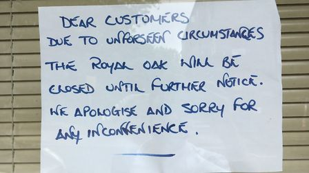 A sign in the window of The Royal Oak pub apologising to customers for the business being closed. Pi