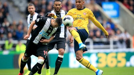Arsenal's Pierre-Emerick Aubameyang (right) and Newcastle United's Javier Manquillo battle for the b
