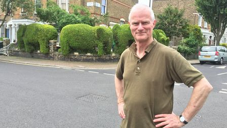 Architect and topiatrist Tim Bushe stand at the junction of Romilly Road and Ambler Road, posing in