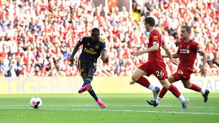 Arsenal's Nicolas Pepe (left) shoots towards goal during the Premier League match at Anfield, Liverp
