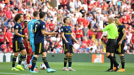 Referee Anthony Taylor (right) awards a penalty after a foul from Arsenal's David Luiz (left) during