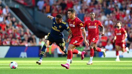 Arsenal's Joe Willock (left) and Liverpool's Roberto Firmino battle for the ball during the Premier