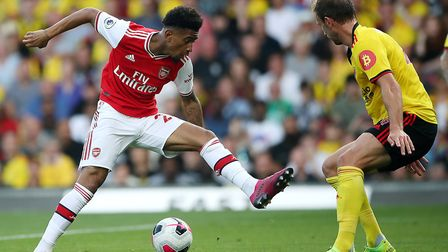 Arsenal's Reiss Nelson (left) and Watford's Craig Dawson battle for the ball during the Premier Leag