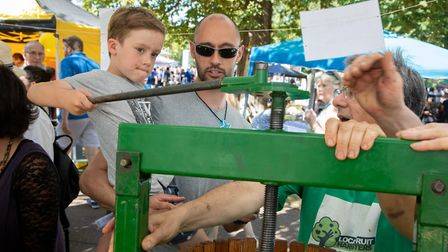 Casper Shaw, four, with dad Alex Shaw pressing apples at the Kensal to Kilburn Fruit Harvesters Grou