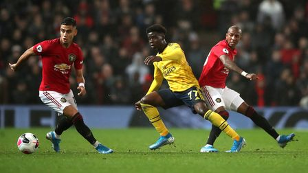 Arsenal's Bukayo Saka in action with Manchester United's Andreas Pereira and Ashley Young during the