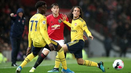 Manchester United's Victor Lindelof battles for the ball with Arsenal's Matteo Guendouzi and Bukayo
