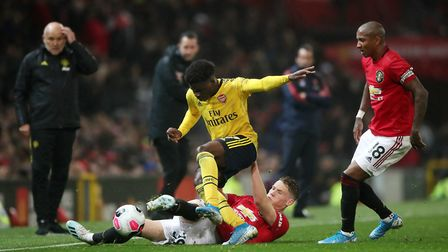 Manchester United's Scott McTominay and Arsenal's Bukayo Saka battle for the ball during the Premier