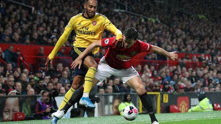 Arsenal's Pierre-Emerick Aubameyang and Manchester United's Harry Maguire battle for the ball during
