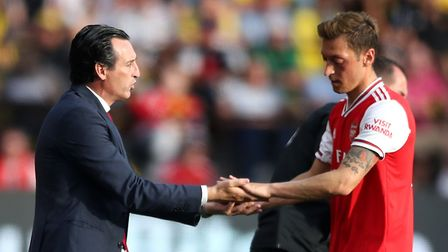 Arsenal manager Unai Emery greets team-mate Mesut Ozil as he is substituted off during the Premier L