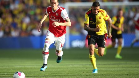 Arsenal's Mesut Ozil (left) and Watford's Jose Holebas during the Premier League match at Vicarage R