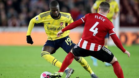 Arsenal's Nicolas Pepe (left) and Sheffield United's John Fleck battle for the ball during the Premi