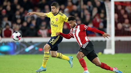 Arsenal's Sokratis Papastathopoulos (left) and Sheffield United's Lys Mousset battle for the ball du