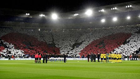 Fans hold up flags for Remembrance Day as the Last Post is played before the Premier League match at