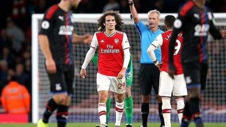 Arsenal's Matteo Guendouzi is shown a yellow card after his tackle on Crystal Palace's Wilfried Zaha