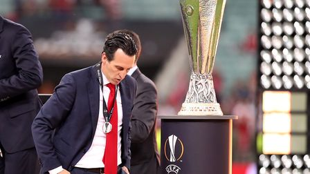Arsenal manager Unai Emery looks dejected as he walks past the trophy after the UEFA Europa League f