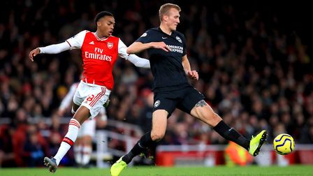 Arsenal's Joe Willock (left) and Brighton and Hove Albion's Dan Burn battle for the ball during the