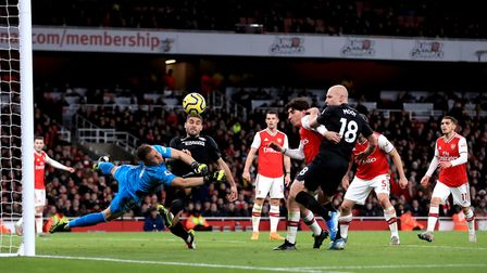 Arsenal goalkeeper Bernd Leno (left) saves a shot from Brighton and Hove Albion's Neal Maupay during