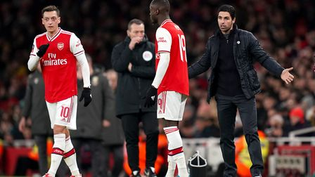 Arsenal Manager Mikel Arteta speaks with Mesut Ozil (left) and Nicolas Pepe on the touchline during