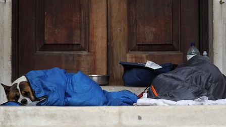 A homeless person and their dog shelter in a doorway in separate sleeping bags, in London. Picture: