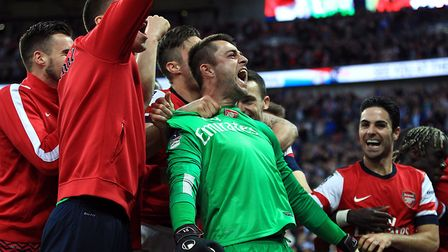 Arsenal's goalkeeper Lukasz Fabianski is mobbed by his team-mates after they win the game on penalty