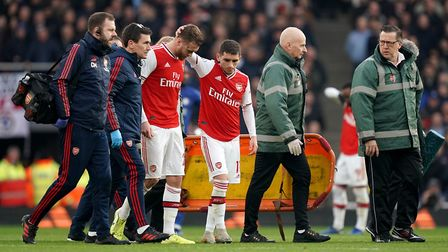 Arsenal's Calum Chambers (centre left) leaves the game after picking up a knee injury during the Pre