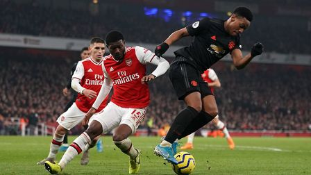 Arsenal's Ainsley Maitland-Niles (left) and Manchester United's Anthony Martial battle for the ball
