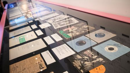 A cabinet displaying song lyrics record releases on display during a preview of The Clash: London Ca