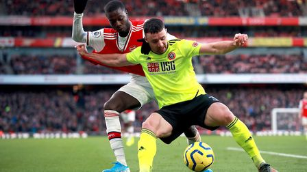 Arsenal's Nicolas Pepe (left) and Sheffield United's Enda Stevens battle for the ball during the Pre