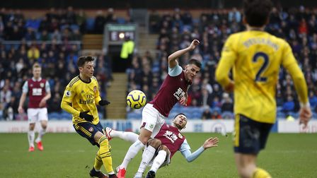 Burnley's Ashley Westwood (centre) and Dwight McNeil (right) battle for the ball with Arsenal's Mesu