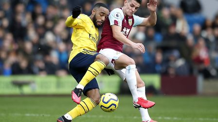 Arsenal's Alexandre Lacazette (left) and Burnley's Ashley Westwood battle for the ball during the Pr