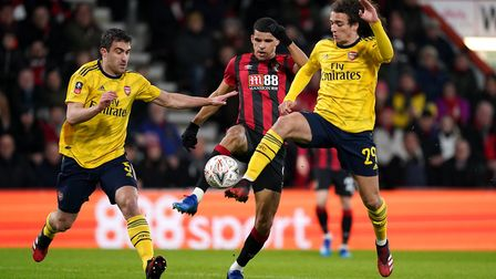 Bournemouth's Dominic Solanke (centre) battles for the ball Arsenal's Sokratis Papastathopoulos (lef