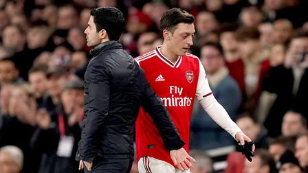 Arsenal's Mesut Ozil (right) is substituted off by manager Mikel Arteta during the Premier League ma