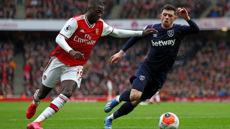 Arsenal's Nicolas Pepe (left) and West Ham United's Aaron Cresswell battle for the ball during the P